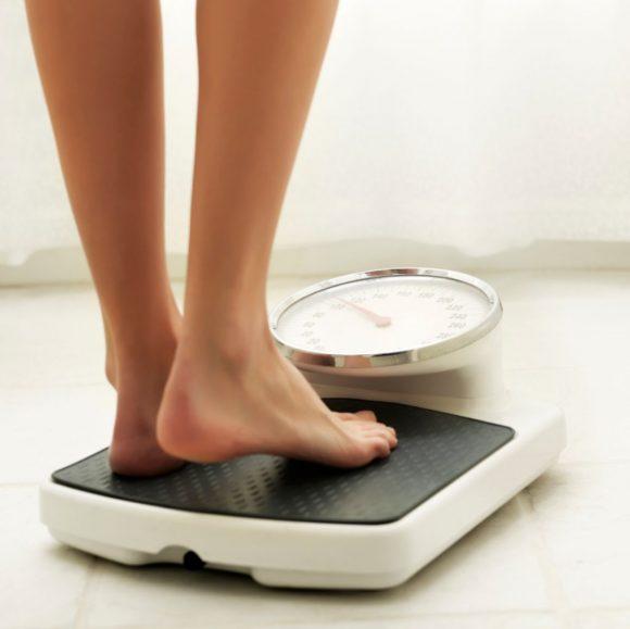 mujer en una balanza intenta bajar de peso