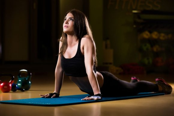 Attractive female athlete stretching on yoga mat in gym.Young and athletic girl in a gym. Stretching fitness and pilates exercise.Young woman doing some pilates exercises